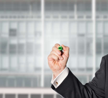 businessman with a green pen, and a ofice background