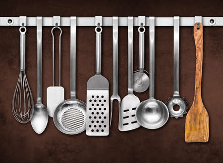 kitchen utensil: Metal rail with kitchen utensils hanging in front of a colorful wall