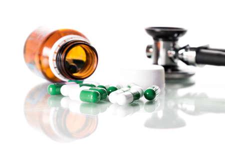 estetoscopio: Puñado de pastillas y un estetoscopio sobre la mesa