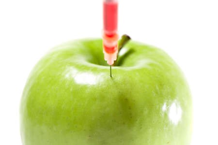 food inspection: Green apple with syringe and red liquid, isolated Stock Photo