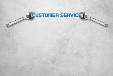 workshop seminar: Wrench holds lettering customer service in front of a gray concrete wall Stock Photo