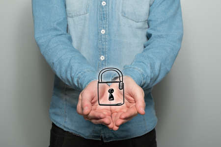two visions: Young man holds a padlock symbol in front of the upper body