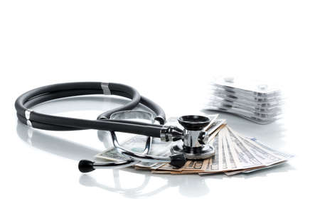 health care costs: Dollar bills with stethoscope and pills on a white table