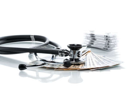 healthcare costs: Dollar bills with stethoscope and pills on a white table