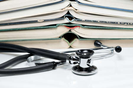 lexicon: Many pitched books are placed in a stack and a stethoscope