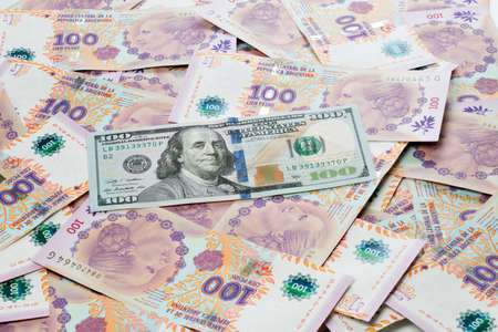 politically: Argentine peso and US dollar bills as a background