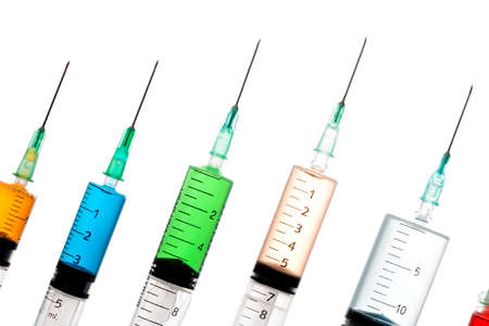 hypodermic syringe: Various syringes filled with colored liquids, closeup isolated Stock Photo