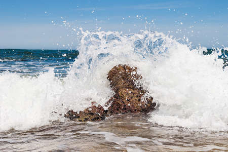 steadfast: Waves breaking on the beach on a rock