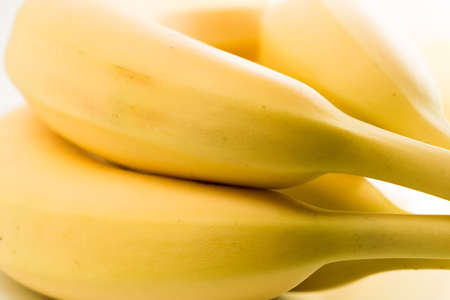 aliments: Four bananas against white background close up