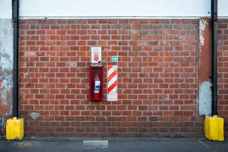 extinguishers: Fire extinguisher hanging on a brick wall with warning signs