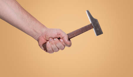 symbolically: Man holding a hammer in his hand in front of a blue background with clipping path Stock Photo