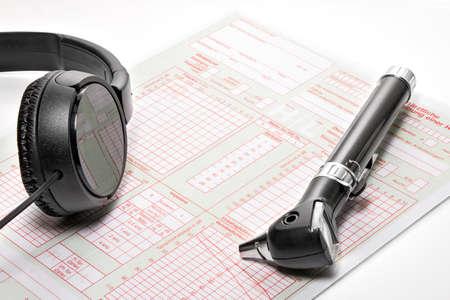 eardrum: Headphones and otoscope lying on an examination form