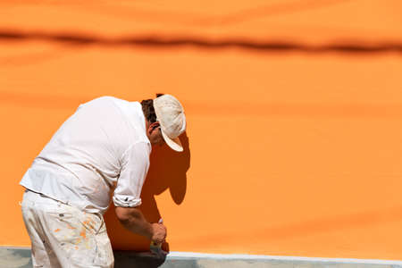 Painters painting a stone wall with orange color