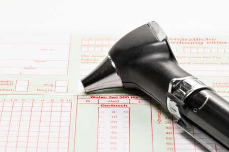 eardrum: Otoscope for ear diagnosis lies on an examination form Stock Photo