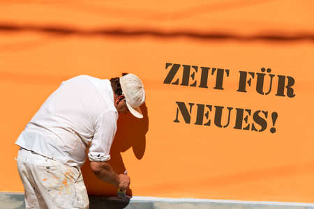 refurbishment: Painters painting a stone wall with orange color, with tehe german words time for a new. Stock Photo