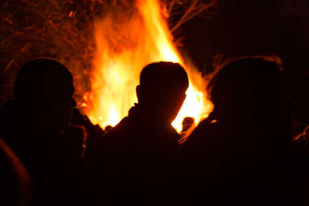 People in front of a large fire with high flames Stock Photo