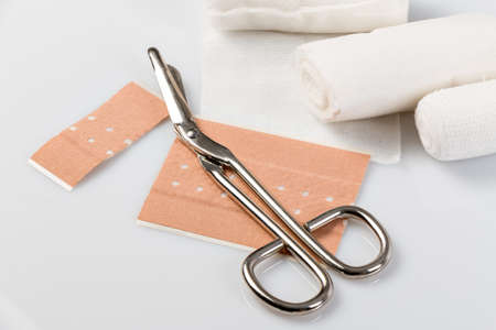 Plasters and bandages with Scissors and syringe on a white background Standard-Bild