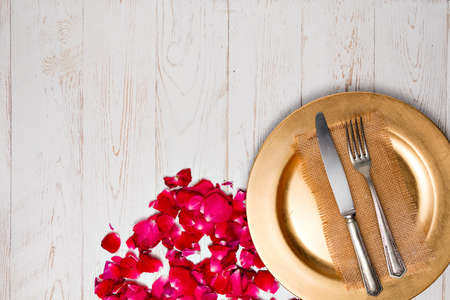 Cutlery on a napkin lying on an old white Decorated with rose petals wooden table