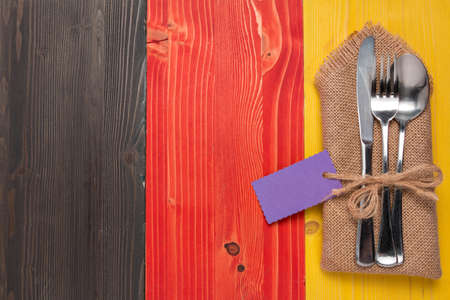Cutlery is in a napkin wrapped on a wooden table in the German national colors Imagens