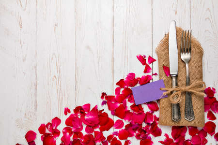 grunge cutlery: Cutlery on a napkin lying on an old white Decorated with rose petals wooden table
