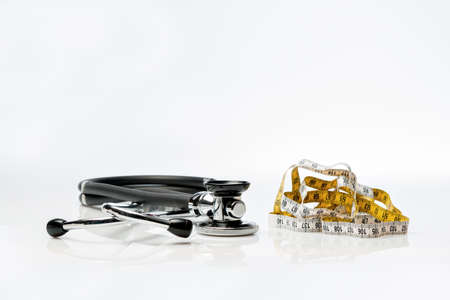 way of living: Stethoscope and tape measure lying on white background