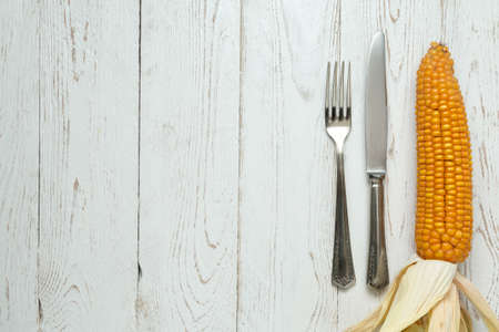 zea mays: Cutlery on old rustic wooden table with corn on the cob (Zea mays) Stock Photo