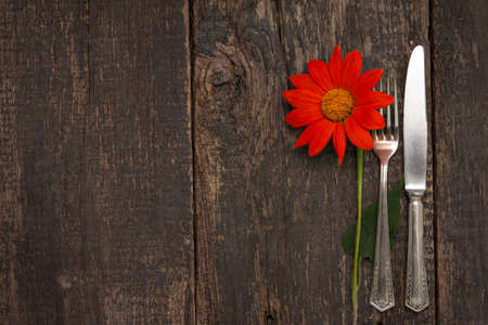 Cutlery is on an old table with a Mexican Sunflower (Tithonia rotundifolia)
