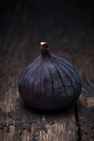 Ripe fig (Ficus carica) lying on old rustic wooden board Stock Photo