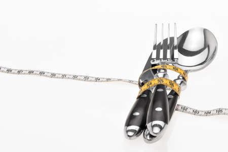 Cutlery, spoon, knife and fork wrapped with a tape measure, symbolic for a diet Stock Photo