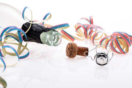 Lying champagne bottle and cork between confetti and streamers