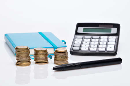 Euro coin pile with pocket calculator and blue notebook