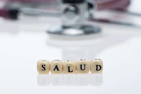 Salud, word written with dice in Spanish, and stethoscope