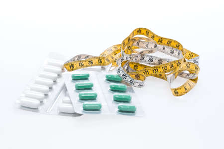 Tape measure and pills on a white table Stock Photo