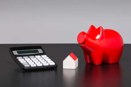 Model house, piggy bank with pocket calculator on a blueprint Stock Photo