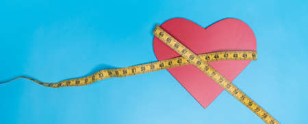 Tape measure, and a red heart on a blue background