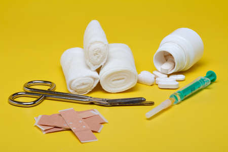Plasters and bandages with Scissors and syringe on a yellow background Reklamní fotografie