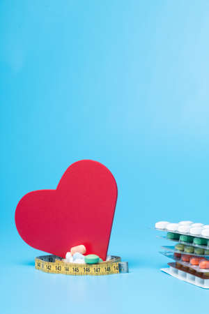 Tape measure, pills and a red heart on a blue background 版權商用圖片