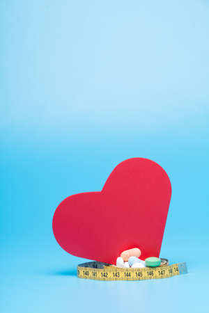 Tape measure, pills and a red heart on a blue background 免版税图像