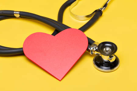 Stethoscope with red heart on yellow background