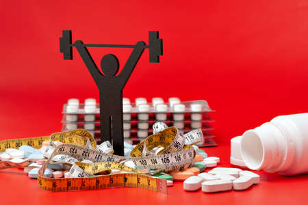 weightlifting pictogram with pills and tape measure, red background Фото со стока