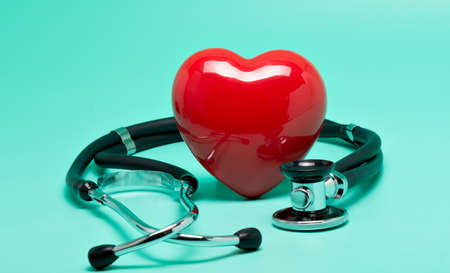 Stethoscope with red heart on bright green background