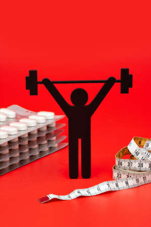 weightlifting pictogram with pills and tape measure, red background Banque d'images