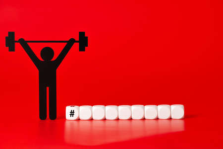 Black weight lifter pictogram with white unlabeled cubes, on red background