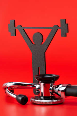 Weight lifting pictogram, Stethoscope, close-up isolated with red background