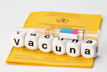 Syringe with vaccine and International Vaccination Passport. Vaccination written with dice. (Vacuna spanish for Vaccinate)