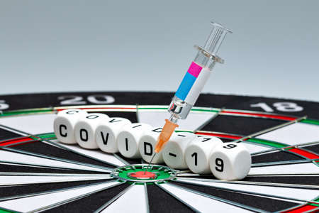 Syringe with Covid-19 vaccine is in the dartboard