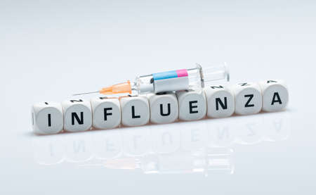 Syringe with flu vaccine lies on cube with text