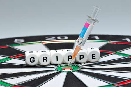 Syringe with flu vaccine is in dartboard