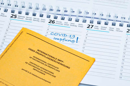 Calendar with one day for COVID-19 vaccination and vaccination certificate (in German) Stock Photo