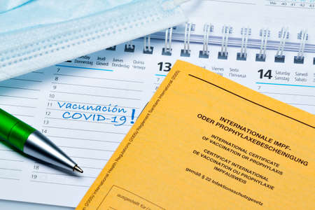Calendar with one day for COVID-19 vaccination and vaccination certificate (in Spanish) Stock Photo